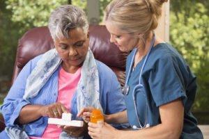 petaluma home care caregiver helping a seated senior woman look at her medication.