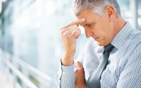 Depressed man with hand on head